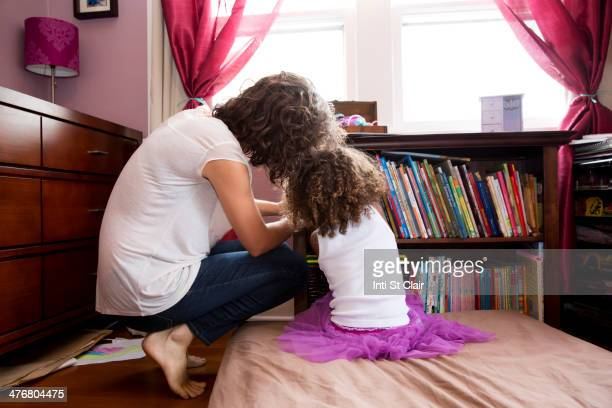 Mother and daughter picking books from shelf