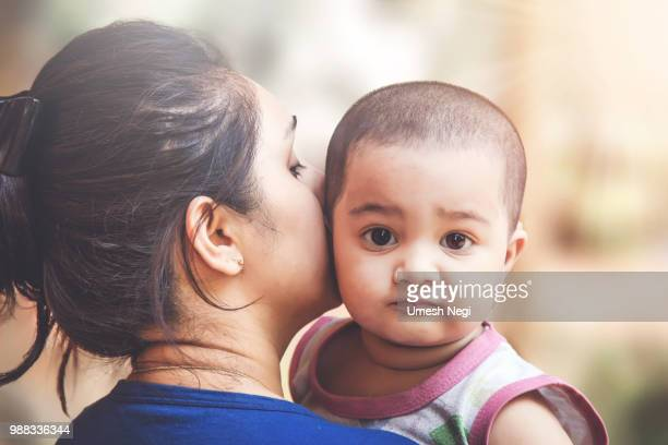 mother and daughter - indian girl kissing stock photos and pictures