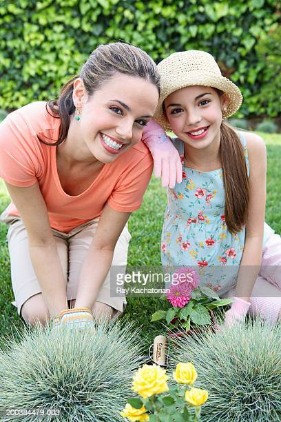 Mother and daughter (10-12) planting dahlias in garden