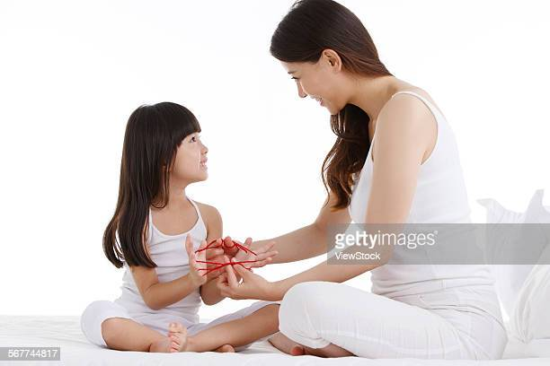 Mother and daughter play cats cradle in the bed of the bedroom