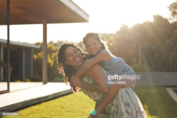 mother and daughter playing and laughing in their garden - soft focus foto e immagini stock
