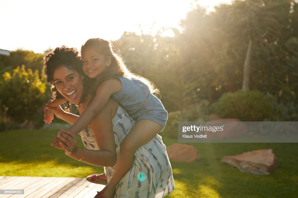 Mother and daughter playing and laughing in their garden : Stock Photo
