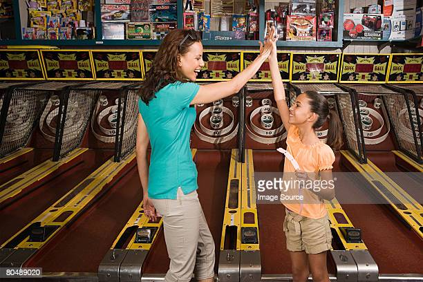 mother and daughter playing arcade game - arcade stock photos and pictures
