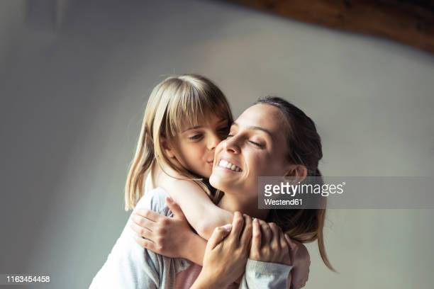 mother and daughter playing at home, piggyback - mother stock-fotos und bilder