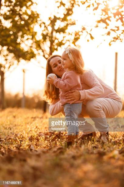Mother and daughter playing at the park on warm autumn day