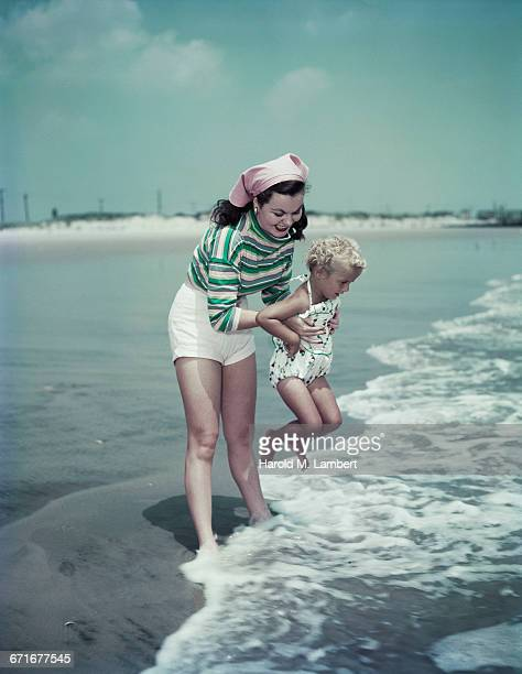mother and daughter playing at water edge   - {{relatedsearchurl(carousel.phrase)}} ストックフォトと画像