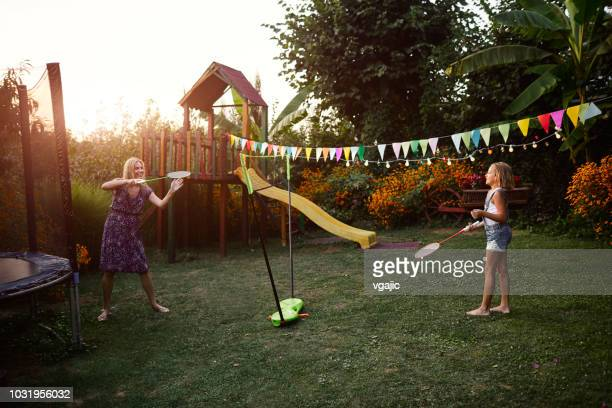 mother and daughter playing badminton in backyard - badminton stock pictures, royalty-free photos & images