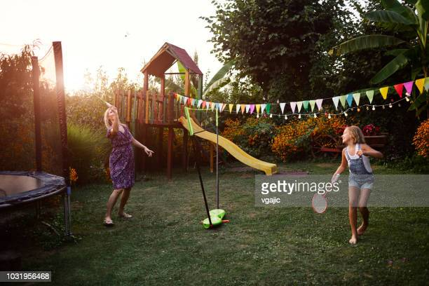 mother and daughter playing badminton in backyard - badminton sport stock photos and pictures