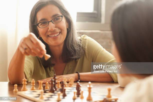 mother and daughter playing chess - playing chess stock pictures, royalty-free photos & images