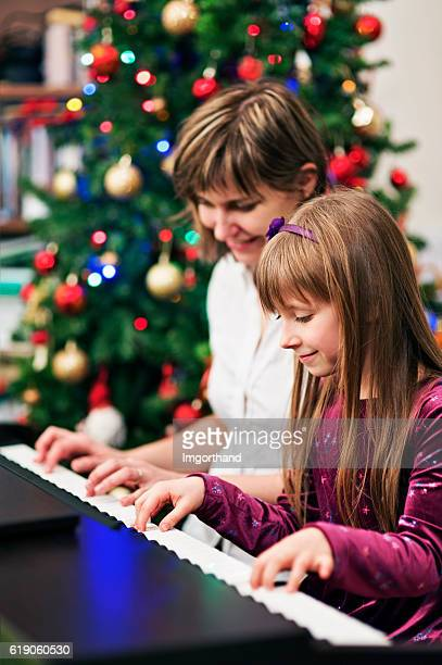 Mother and daughter playing christmas carols on piano