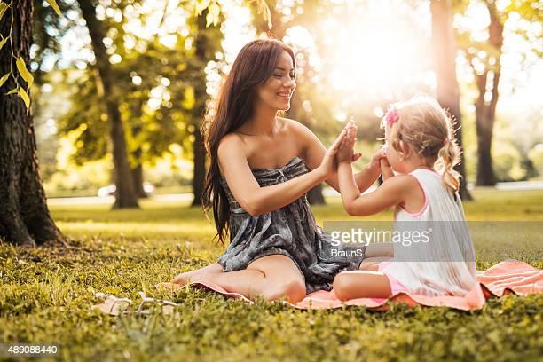 Mãe e filha Jogando Jogo de Bater Palmas durante a Primavera dia.