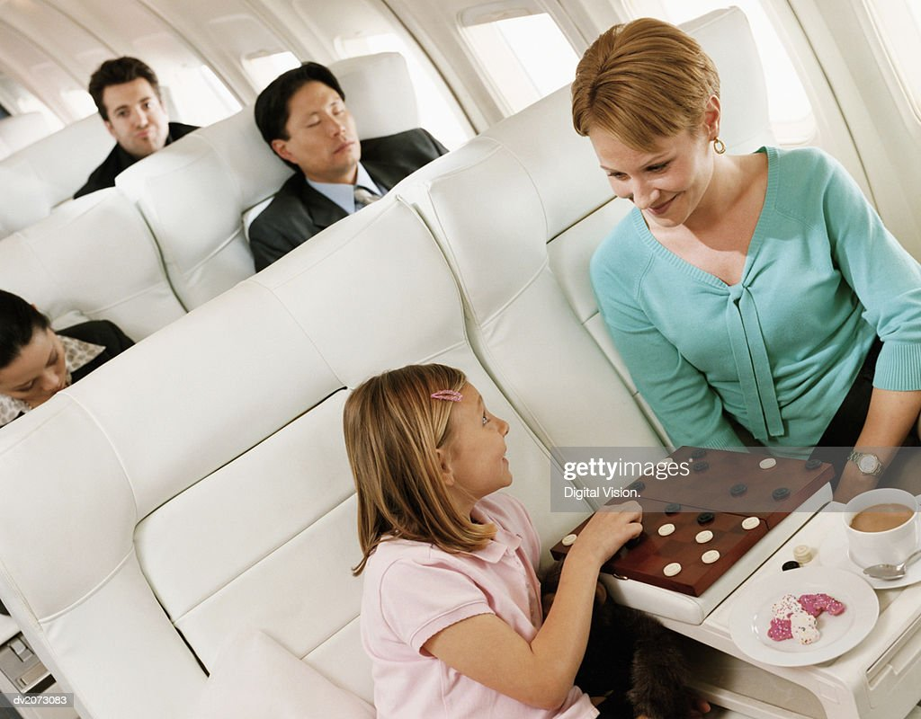 Mother and Daughter Playing Draughts, and Passengers in the Background in an Aircraft Cabin Interior : Stock Photo