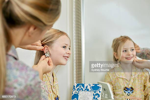 Mother and daughter playing dress-up in bedroom