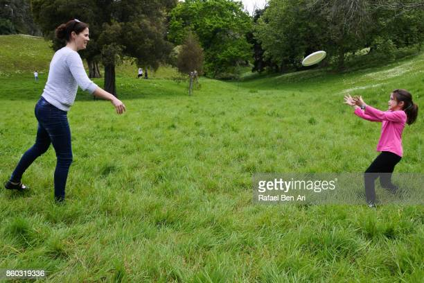Mother and daughter playing frisbee in the park