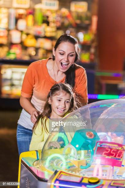 mother and daughter playing game in amusement arcade - arcade stock photos and pictures