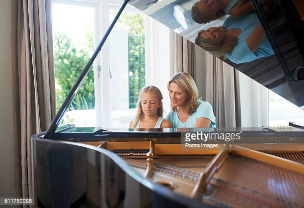 Mother and daughter playing grand piano