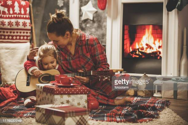 mother and daughter playing guitar together on a christmas eve - christmas music stock pictures, royalty-free photos & images