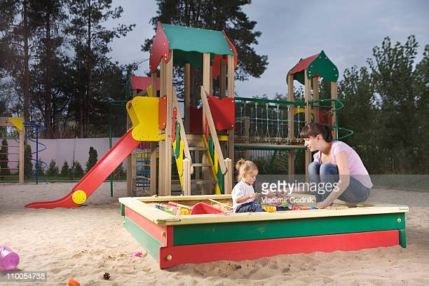 a mother and daughter playing in a sandbox - spielgerät stock-fotos und bilder