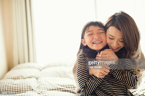 mother and daughter playing in bed room - asien stock-fotos und bilder