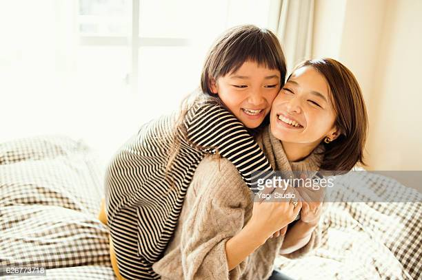 mother and daughter playing in bed room - 30代 ストックフォトと画像