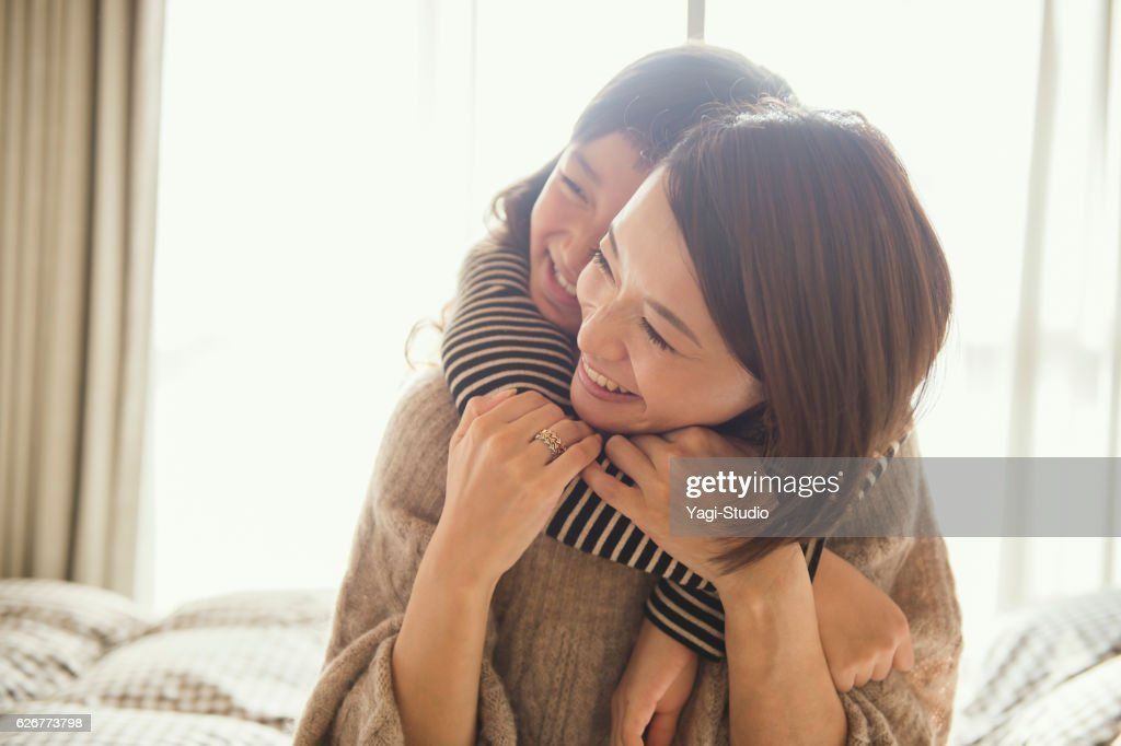 Mother and daughter playing in bed room : Stock-Foto