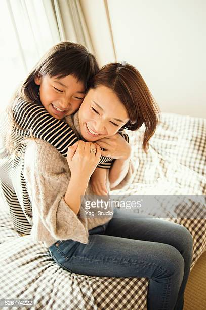 Mother and daughter playing in bed room