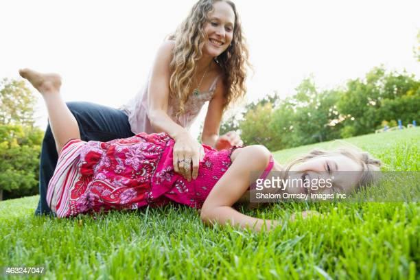 mother and daughter playing in grass - kitzeln stock-fotos und bilder