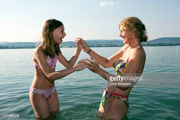 mother and daughter playing in lake - preadolescent kind stockfoto's en -beelden