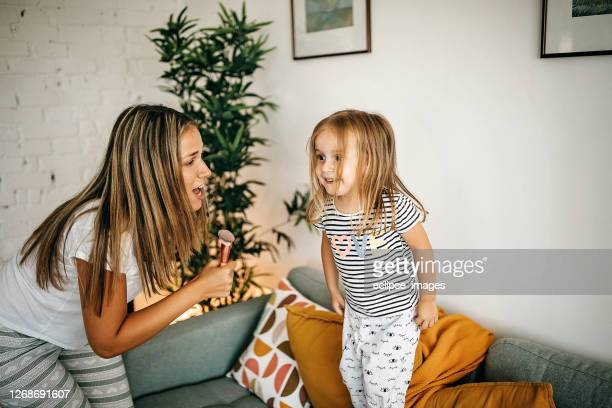 mother and daughter playing in living room - singing stock pictures, royalty-free photos & images