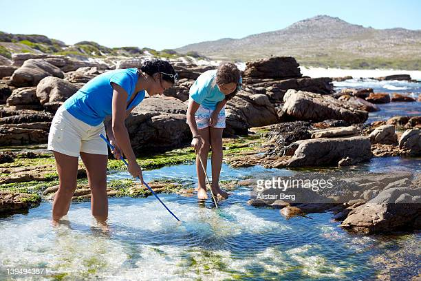 Mother and daughter playing in rockpool