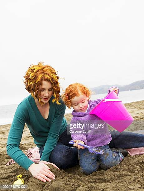 mother and daughter (2-4) playing in sand on beach - schiff stock photos and pictures