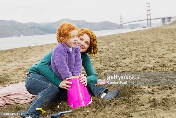 mother and daughter (2-4) playing in sand on beach - caroline roux photos photos et images de collection