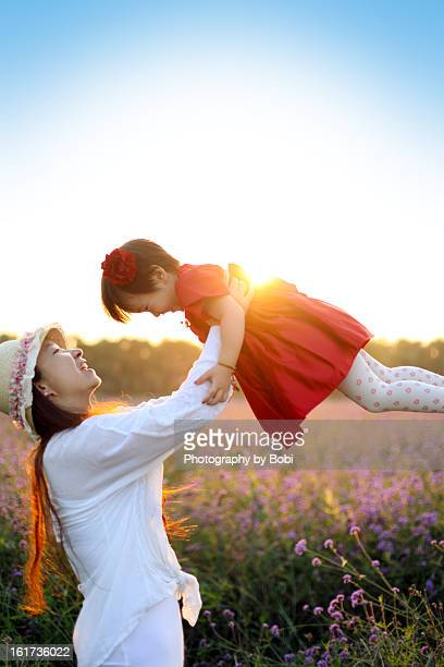 Mother and daughter playing in the flowers