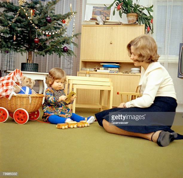 Mother and daughter playing in the living room at Christmas
