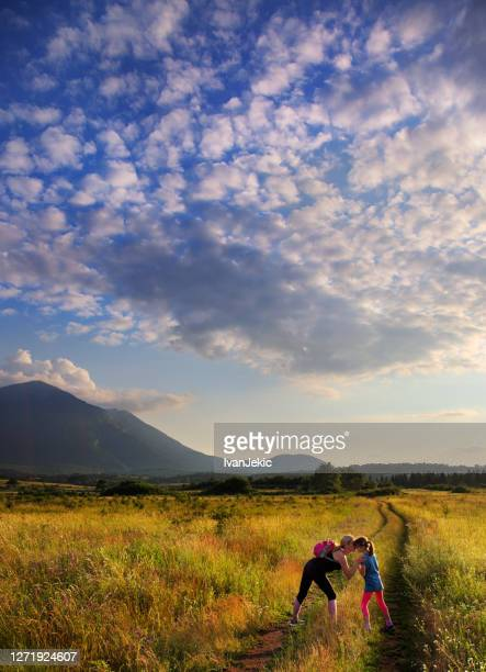 mother and daughter playing in the mountain field - ivanjekic stock pictures, royalty-free photos & images