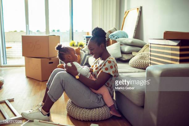 mother and daughter playing in their new home - daughter stock pictures, royalty-free photos & images