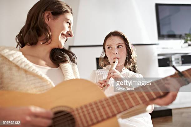 Mother and daughter (7-9) playing musical instruments in home