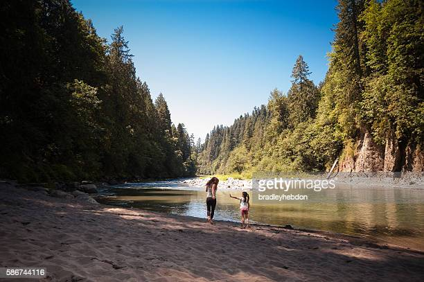 Mother and daughter playing near river in forest