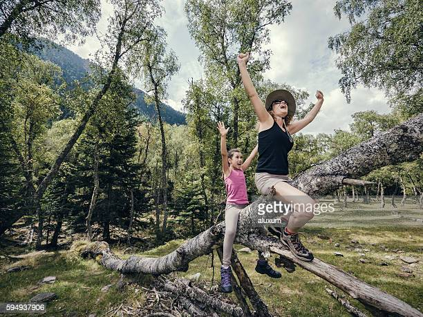 Mother and daughter playing on a fallen tree