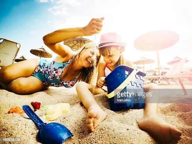 Mutter und Tochter spielen am Strand mit sand und Spielzeug