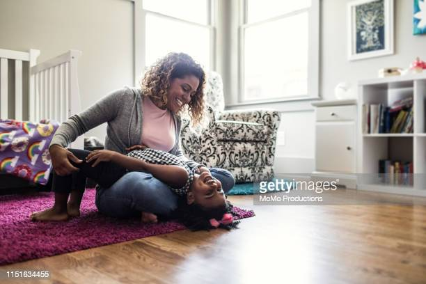 mother and daughter playing on bedroom floor - single mother stock pictures, royalty-free photos & images