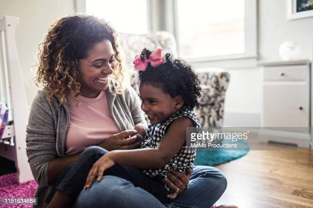 mother and daughter playing on bedroom floor - adulto de mediana edad fotografías e imágenes de stock