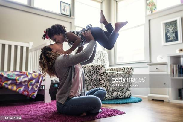 mother and daughter playing on bedroom floor - puerto rican ethnicity stock pictures, royalty-free photos & images