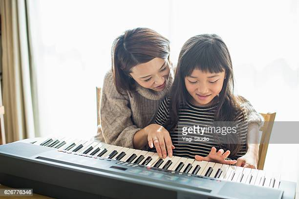 Mother and daughter playing  on electronic piano