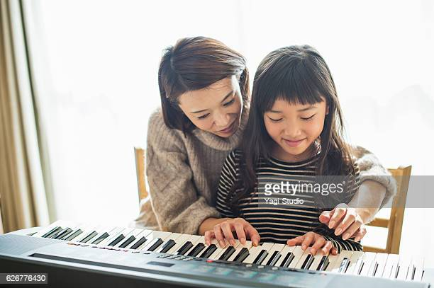 mother and daughter playing  on electronic piano - ピアノ ストックフォトと画像