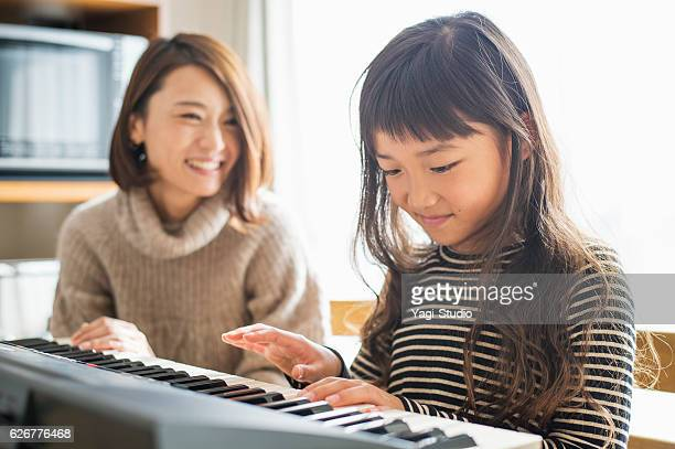mother and daughter playing  on electronic piano - electric piano stock photos and pictures