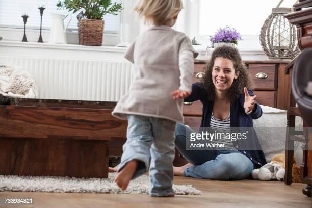 mother and daughter playing on floor - strickjacke stock-fotos und bilder