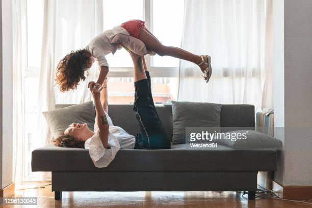 mother and daughter playing on sofa - bonding stock pictures, royalty-free photos & images