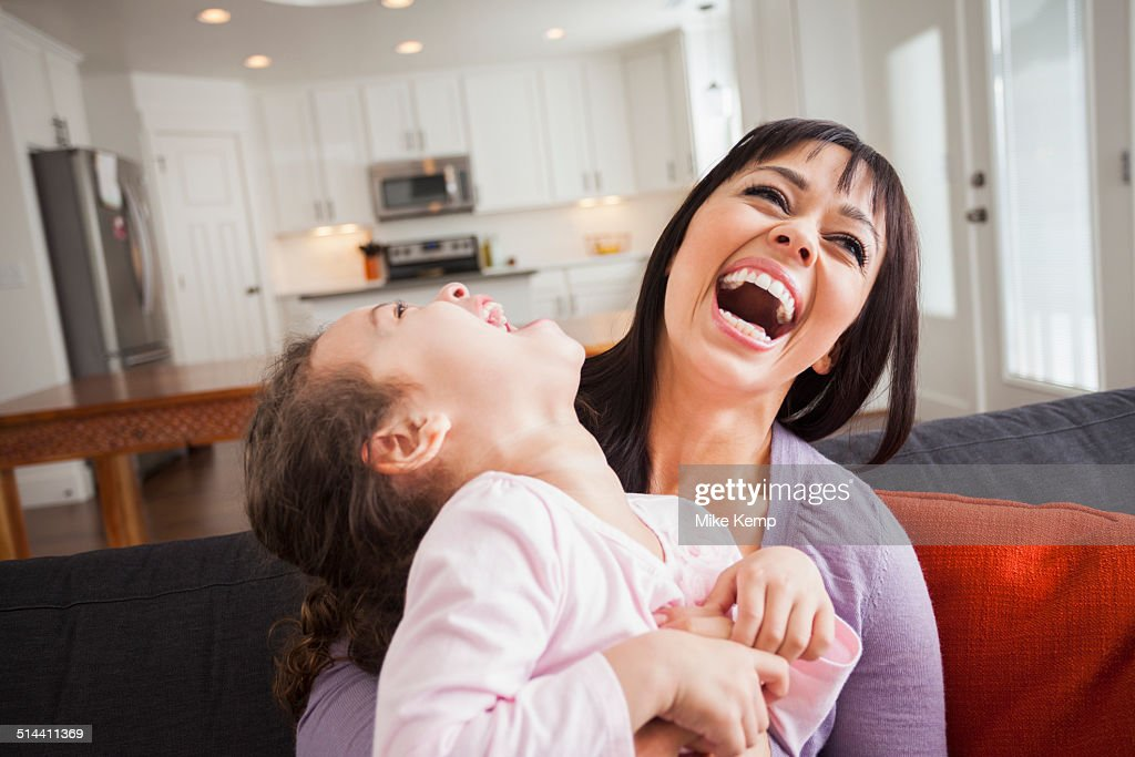 Mother and daughter playing on sofa : Stock Photo