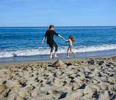 mother daughter playing beach